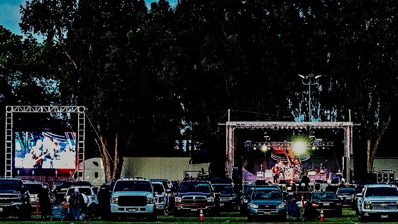 people outside their cars attending a drive-in concert featuring a mobile stage and LED screen on a truss structure